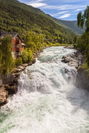 Waterfall, mountains and house in Lom, Norway