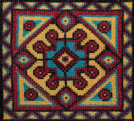 Cross-stitch handmade embroidery. The round colorful pattern. Stock Photo