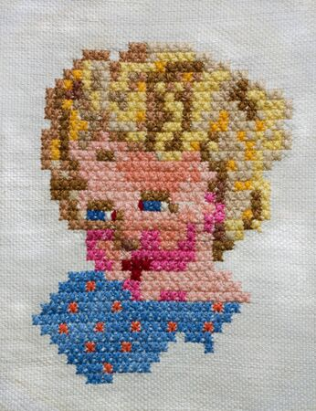 Cross-stitch handmade embroidery. The colorful babys head.