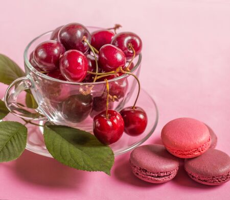 Cherries in the glass cup with macaroons and leaves Stock Photo