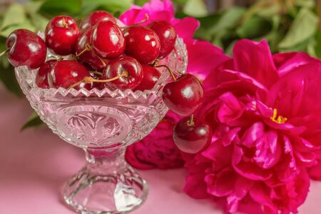 Cherries in the beautiful crystal vase with peony