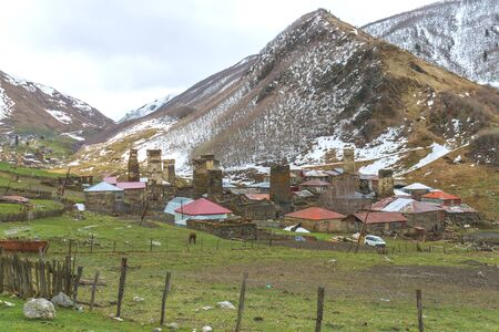 Ushguli village against the snow-capped peaks in the backdrop, Svaneti, Georgia Stock Photo