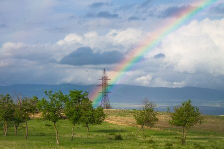 Beautiful landscape with rainbow over power pylon