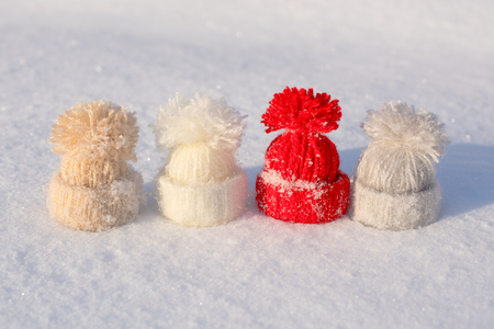 hi hat: Tiny khitted hats on snow. Winter background Stock Photo