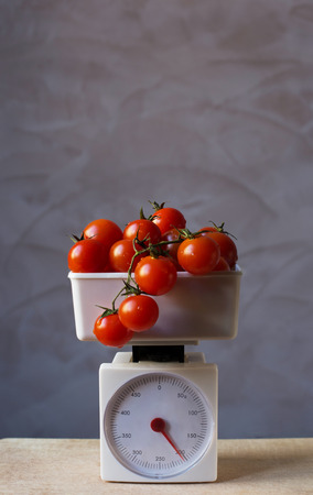 red gram: Tomatoes on scale Stock Photo