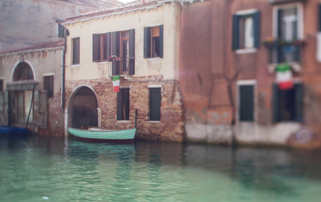 brige: Tilt shift photo of Venice street with boat and flag
