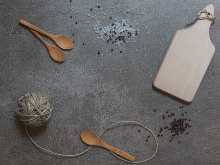 clew: Wooden spoons, cutting board and clew on the stone background