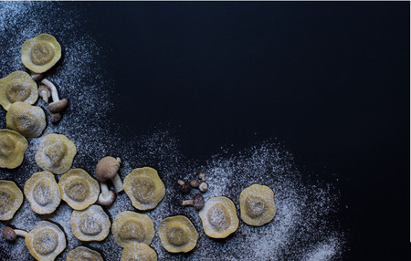 torment: Homemade tortellini with mushrooms on black background. Top view Stock Photo