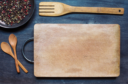 condiment: Wooden spoons with cutting board and condiment on dark background Stock Photo