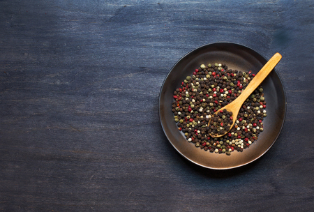 condiment: Plate with condiment and wooden spoon on dark background