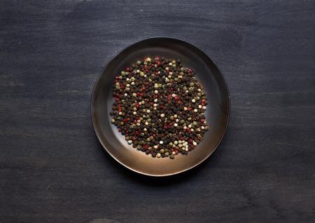 pepe nero: Tavola con condimento su sfondo di legno scuro