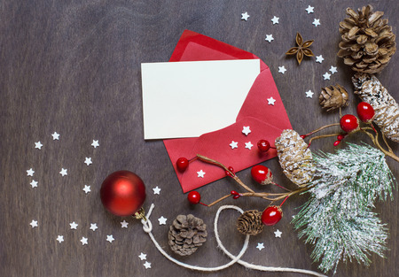 envelope: Christmas background with red envelope, invitation card, decoration and sugar stars on wooden background. Top view