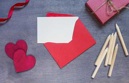 two on top: Red envelope with a gift and two wooden hearts. Top view. Stock Photo