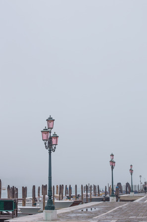 improbable: Some rose lamps on canal in fog Venice, Italy Stock Photo