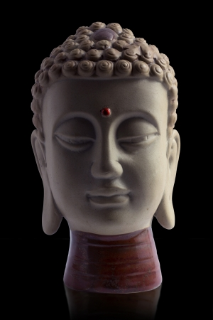 Buddha face with reflex and black background photo