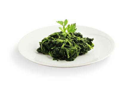 A ceramic plate with spinach and parsley Stock Photo