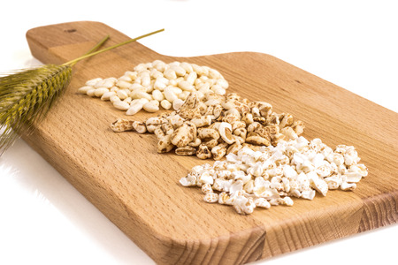 Wooden cutting board with over wheat, spelled, barley and rice crispies Stock Photo