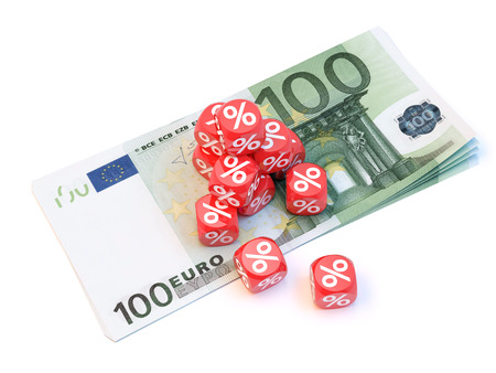 percentages: Group a percentage dice over a pile of 100 euros. Stock Photo