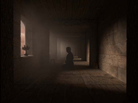 dimly: Devotee prays in a dimly lit corridor of a temple