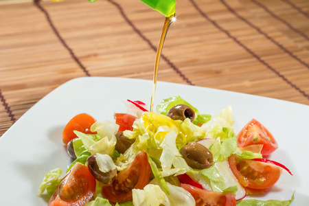 vegan lettuce salad with tomatoes, radishes and olives oil