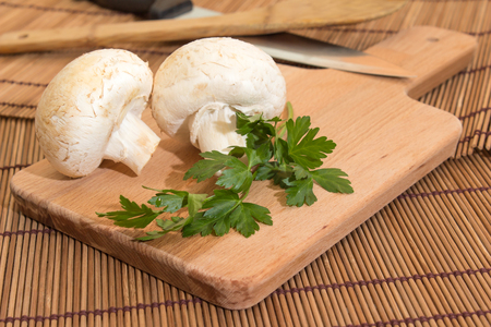 Mushroom on a cutting board with parsley Stock Photo