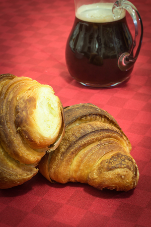 Two croissants on a table with coffee in the background