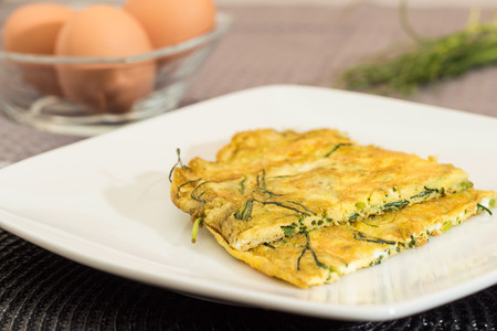 Agretti omelet with fresh ingredients in the background