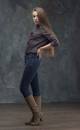 Pretty young woman in casual style standing in full length on dark background photo