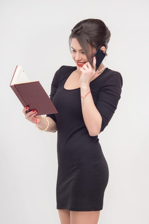enticing: Enticing attractive young brunette woman standing with book in full length in black dress, isolated on white background
