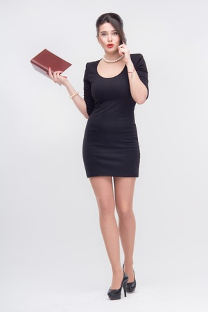tempting: Tempting attractive young brunette woman standing with book in half length in black dress, isolated on white background