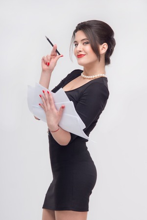 enticing: Enticing attractive young brunette woman standing with documents in half length in black dress, isolated on white background