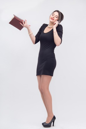cheery: Tempting attractive young brunette woman standing with book in half length in black dress, isolated on white background