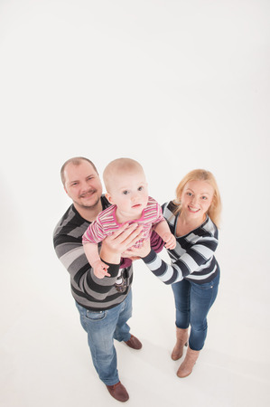 pullovers: Smiling mother and father in striped pullovers lifting up baby boy. Top view isolated portrait on the white background. Family concept. Stock Photo