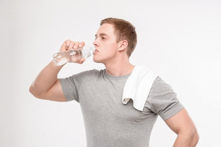 Young muscled man drinking water after workout isolated on white background photo
