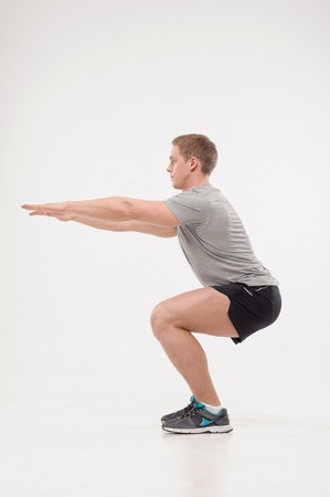 Athletic young handsome man doing squats, isolated on white  Concept of sport, health photo