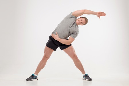 keeping fit: Full length portrait of young smiling man athlete doing warming exercises isolated on white background  Concept of sport, health, keeping fit Stock Photo