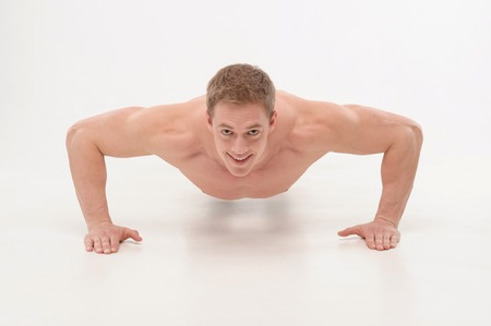 keeping fit: Young sportsman, fitness muscle model guy making push ups exercise isolated on white  Concept of sport, keeping fit
