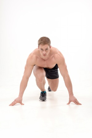 keeping fit: Full length portrait of young man athlete doing running  exercises isolated on white background  Concept of sport, health, keeping fit