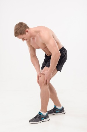Young  sportsman, fitness muscle model guy feeling pain in his knee isolated on white background  Concept of sport, pain photo