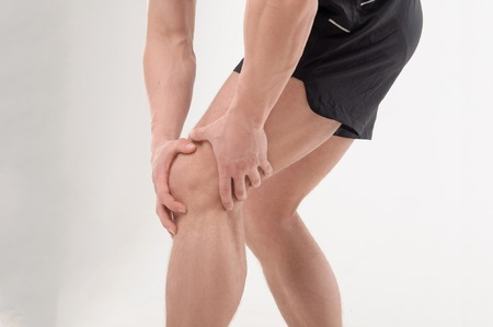 sports medicine: Young  sportsman, fitness muscle model guy feeling pain in his knee isolated on white background  Concept of sport, trauma Stock Photo