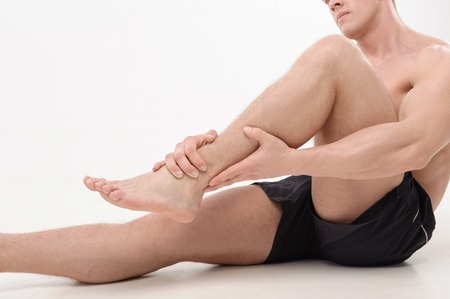 Young  sportsman, fitness muscle model guy feeling pain in his ankle isolated on white  Concept of sport, pain photo