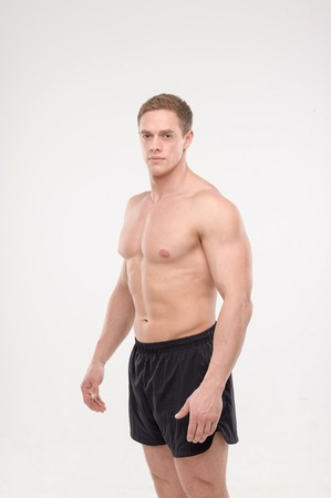 naked man: Shirtless healthy athletic smiling young man side view portrait, isolated on white background