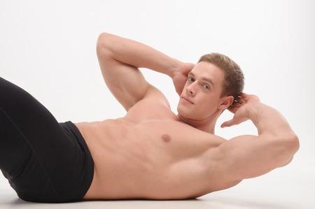 Man athlete doing fitness, abdominal exercises  Isolated on white background photo