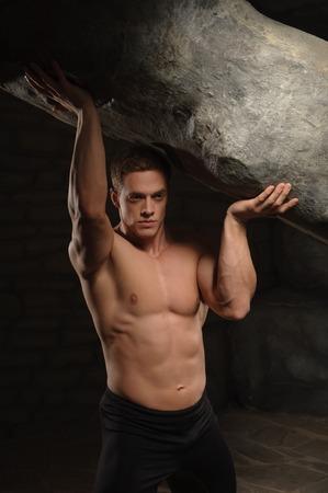 oppressed: Strong muscular man athlete atlant holding huge stone  Half length portrait  Symbol of power, burden