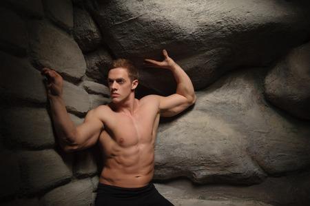 burdensome: Strong muscular man athlete atlant holding huge stone  Half length portrait  Symbol of power, burden