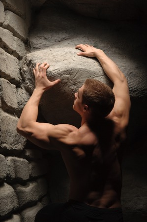Strong muscular man athlete atlant holding huge stone  Half length portrait  Symbol of power, burden photo