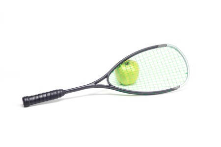 Green apple behind sport racket isolated on white photo