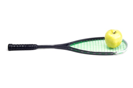 Green apple over sport racket isolated on white photo
