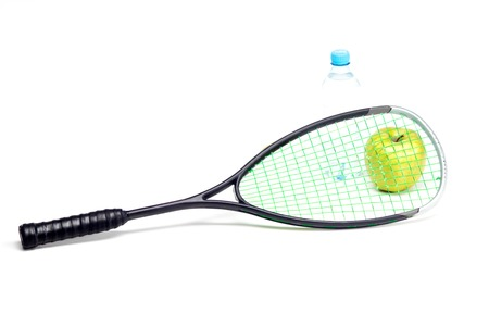 Green apple and water bottle behind sport racket isolated on white photo