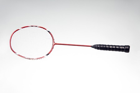 Red badminton racket isolated over grey background photo